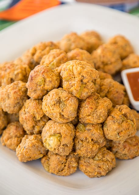 Mexican Sausage Balls - our favorite sausage balls kicked up with taco seasoning and green chiles. Can make ahead of time and freeze unbaked for a quick snack later. Serve with some salsa or a mixture of salsa and ranch. SO GOOD!!! These things fly off the plate at parties! Perfect for tailgating!! We love this easy Mexican appetizer recipe!