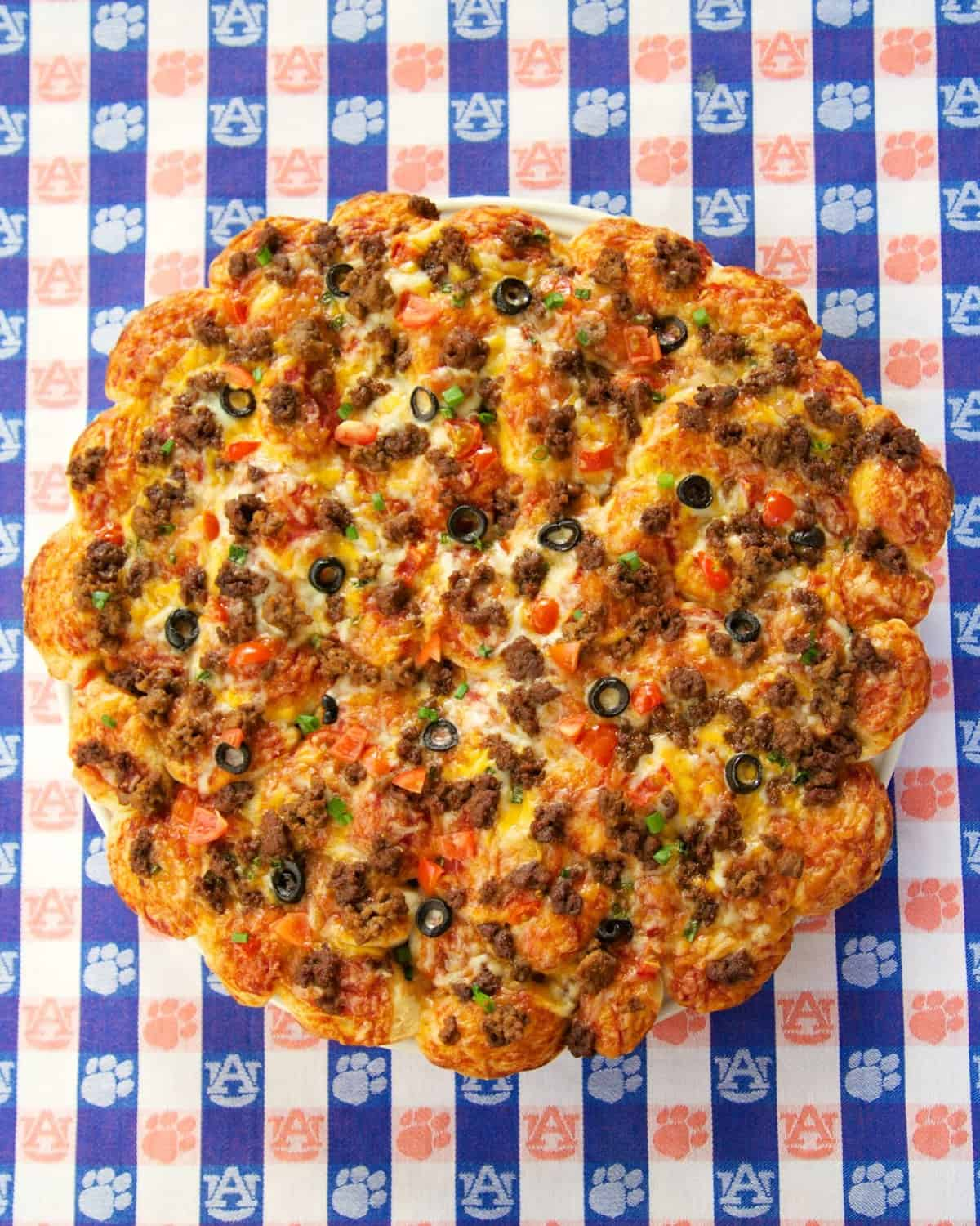 Mexican Pull Apart Pizza - refrigerated bread dough, topped with taco sauce, taco meat, cheese, olives, tomatoes and green onions. Great for a party or quick lunch or dinner. Kids (and adults) go nuts over this pizza!