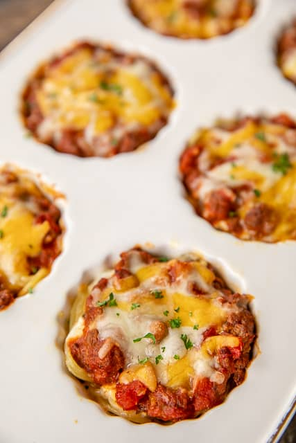 Mini Taco Spaghetti Pies - two favorites combined into one delicious dish!!! Bake in a muffin pan for a fun meal! Spaghetti, eggs, parmesan cheese, ground beef, taco seasoning, Rotel diced tomatoes and green chiles, spaghetti sauce, cottage cheese, butter, cheddar cheese. Can freeze leftovers for a quick meal later. Since they are small, they reheat in a flash! Our new favorite way to eat tacos and spaghetti! #tacos #spaghetti #freezermeal #recipe #spaghettipie #pasta