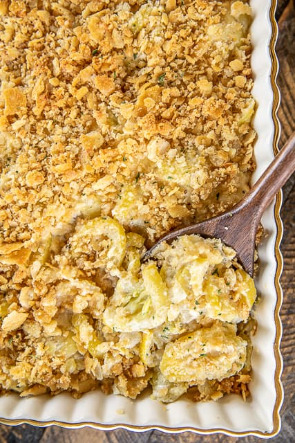 Old School Squash Casserole - a must for your holiday table!!! Loaded with 3 types of cheeses - cheddar, Swiss and parmesan. Seriously delicious! Squash, onion, butter, eggs, sour cream, mayonnaise, cheddar, swiss, thyme, salt, pepper, crushed Ritz crackers and parmesan. Can make ahead of time and refrigerate overnight. SO easy and SO delicious! Everyone LOVES this yummy side dish. #casserole #squash #sidedish #thanksgiving #christmas