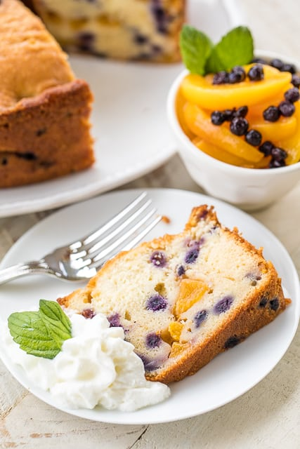 Peach and Blueberry Pound Cake - the perfect summer dessert! Can make ahead of time and serve a few days later. You can even freeze the cake!! Butter, cream cheese, sugar, eggs, milk, flour, baking powder, salt, fresh peaches, fresh blueberries and peach preserves. This cake is CRAZY good! Everyone raves about ti when I take it to a potluck!!