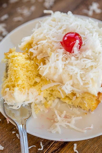 Pina Colada Poke Cake - cake loaded with coconut, pineapple and rum. This cake is SO good!! It gets better as it sits in the refrigerator. Pineapple cake topped with homemade cream cheese frosting and coconut! Golden Butter Cake Mix, oil, eggs, crushed pineapple, sour cream, rum extract, cream of coconut, cream cheese, milk, powdered sugar, coconut. Great for parties and potlucks. There are NEVER any leftovers!! SO good!! #cake #pinacolada #pokecake