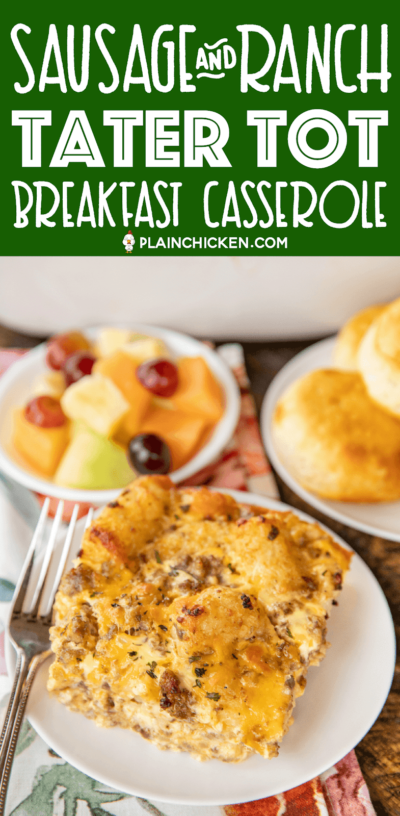 breakfast casserole slice on a plate next to fruit and biscuits