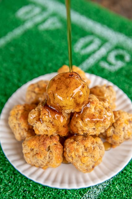 Sausage Pancake Bites - perfect for breakfast, lunch, dinner or parties! Can make in advance and freeze unbaked for later. Only 4 ingredients - sausage, cheese, maple syrup and pancake mix. Mix in your KitchenAid stand mixer and they come together in minutes. Serve with syrup and hot sauce. #sausageballs #freezermeal #makeahead #sausage #recipe