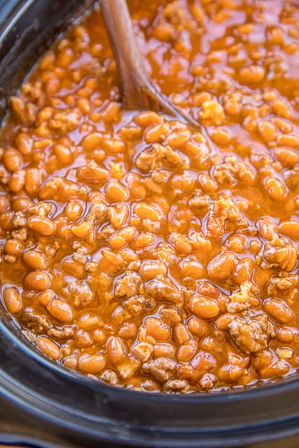 Slow Cooker Cowboy Beans - seriously the BEST baked beans I've ever eaten!!! Loaded with beef and bacon. SO easy to make! Great for potlucks and cookouts. Ground beef, bacon, onion, baked beans, ketchup, mustard, beef broth, garlic, brown sugar. I took these to a cookout and everyone asked for the recipe. A new favorite!! #slowcooker #bakedbeans #cookout #sidedish