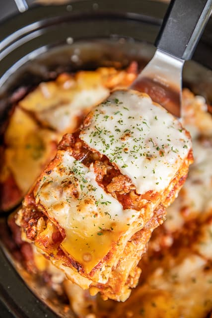 Slow Cooker Lasagna - our favorite lasagna recipe made in the slow cooker! SO easy! No need to boil the noodles - just toss them in the slow cooker unbaked.They will cook along with the lasagna in the slow cooker. Italian sausage, cottage cheese, egg, parsley, spaghetti sauce, tomato sauce, lasagna noodles, mozzarella and parmesan. Serve with some garlic bread and a salad. Can freeze leftovers for later. We LOVE this lasagna casserole recipe!!! #crockpot #slowcooker #lasagna