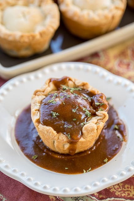 Mini Steak & Ale Pies - Guinness pot roast in pie crust baked in a muffin pan. Inspired by our trip to London, England. These taste better than any of the meat pies we ate in the London pubs. YUM! Slow cooked pot roast, pie crust and Guinness gravy. Can make ahead and freeze for a quick meal later! #london #guinness #steak #meatpie