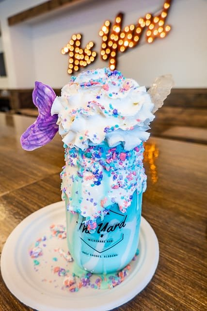 Crazy Shakes from The Yard in Gulf Shores, AL - The Mermaid - Birthday cake ice cream inside a marshmallow cream dipped jar. Topped with whipped cream, marshmallow cream, mermaid candy jewels, rock candy stick and white chocolate mermaid tail