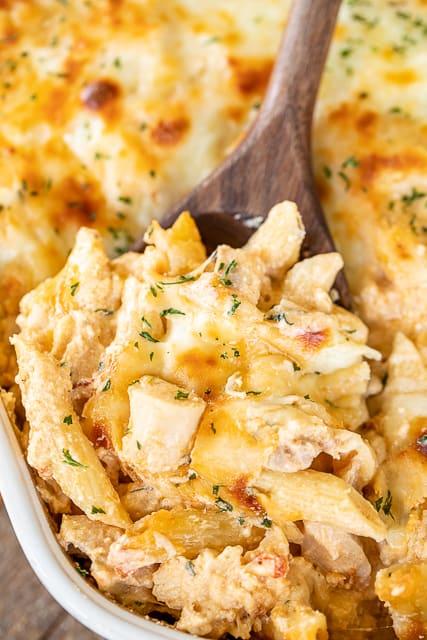 scooping chicken pasta from casserole dish