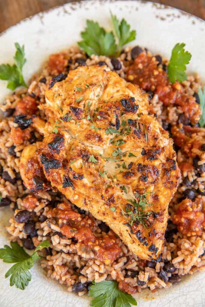 grilled chicken on a plate with rice & beans