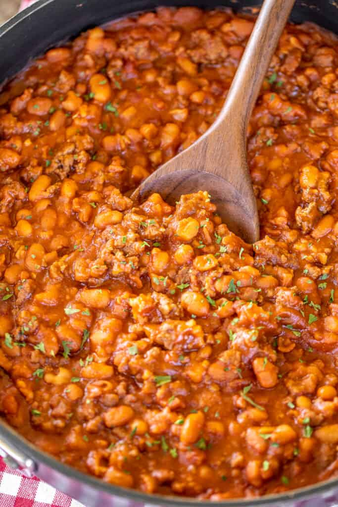 spooning baked beans from skillet