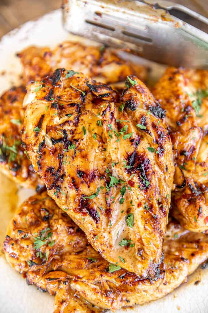 grilled chicken on a plate with tongs