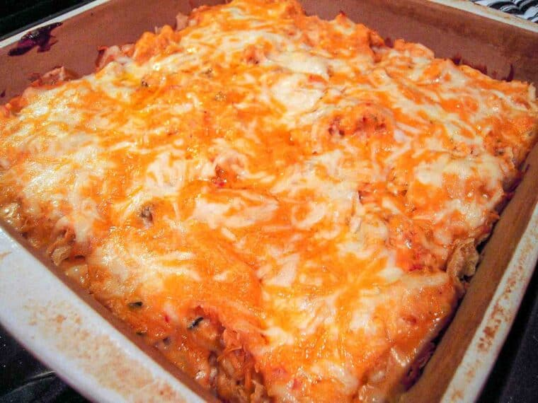 King Ranch Chicken Casserole - Tex-Mex comfort food at its best! Chicken, chicken soup, mushroom soup, onion, diced tomatoes and green chiles, Cheez Whiz, hot sauce, Worcestershire sauce, tortilla chips, cheddar cheese and mozzarella cheese. One of the best things you'll ever eat!! Everyone LOVES this yummy Tex-Mex casserole!! #casserole #chicken #texmex