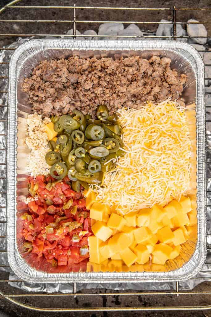 queso ingredients in foil pan on grill