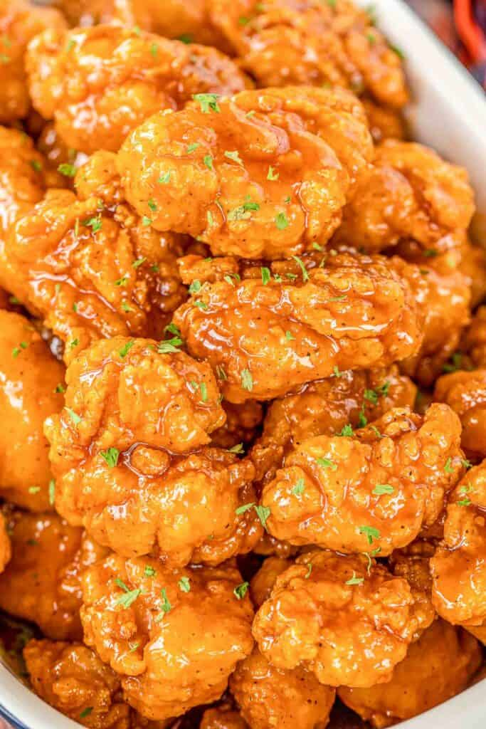 Sweet & Spicy Boneless Wings - great for parties or a quick lunch/dinner. Use frozen chicken bites and this comes together in no time!! Chicken tossed in hot sauce, brown sugar and butter. Seriously delicious!! Serve with fries and ranch or bleu cheese dressing. These are always the first thing to go at our football parties! #chicken #wings #tailgating #partyfood