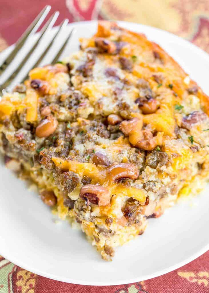 Black Eyed Pea Cornbread Casserole recipe - homemade cornbread loaded with sausage, creamed corn, cheddar cheese, black eyed peas, green chiles, and jalapeños. Perfect for your New Year's Day meal! Can make ahead of time and freeze for up to a month. Everyone LOVES this easy one pan meal! #casserole #cornbread #freezermeal