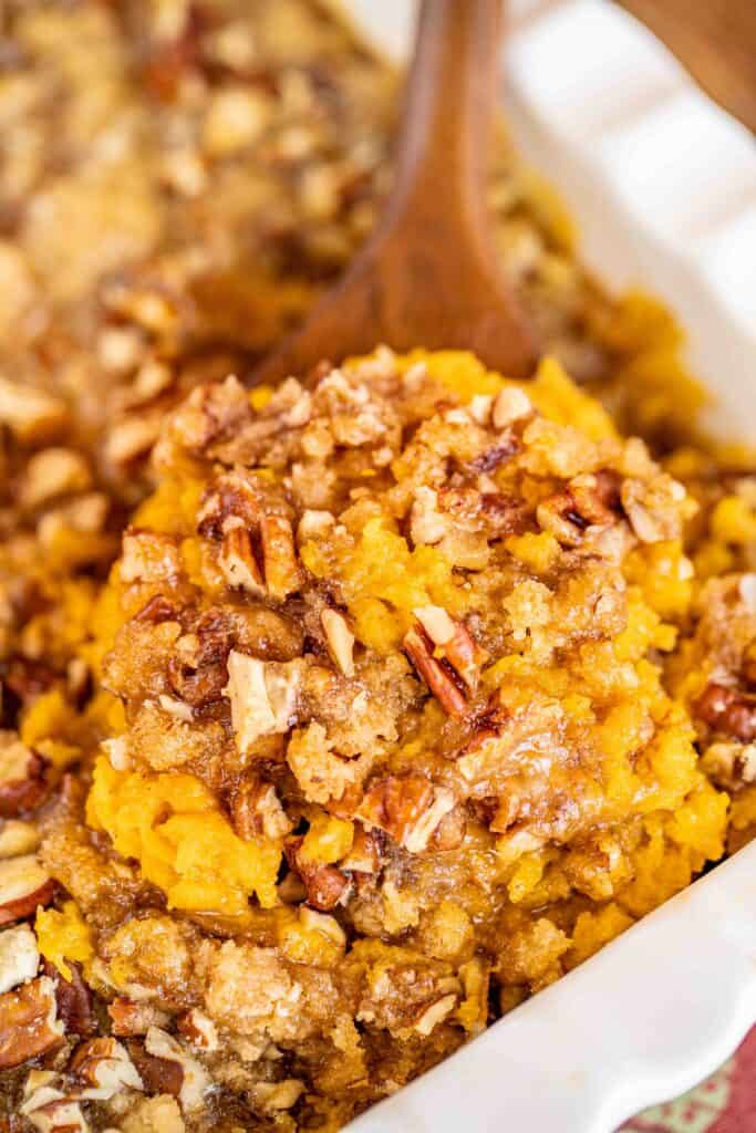 scooping butternut squash casserole from baking dish