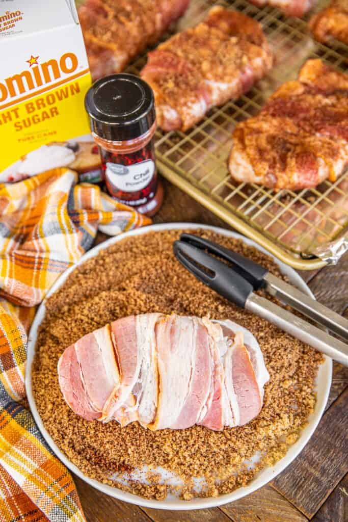 bacon wrapped pork chops being rolled in brown sugar and chili powder