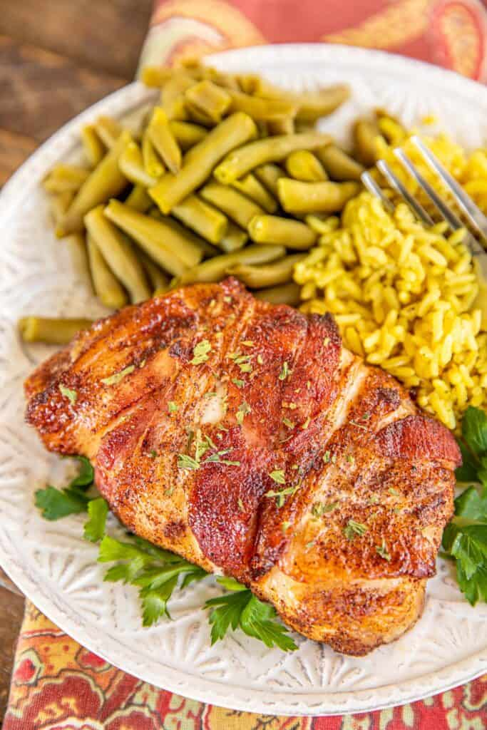 plate of bacon wrapped pork chops with rice and green beans