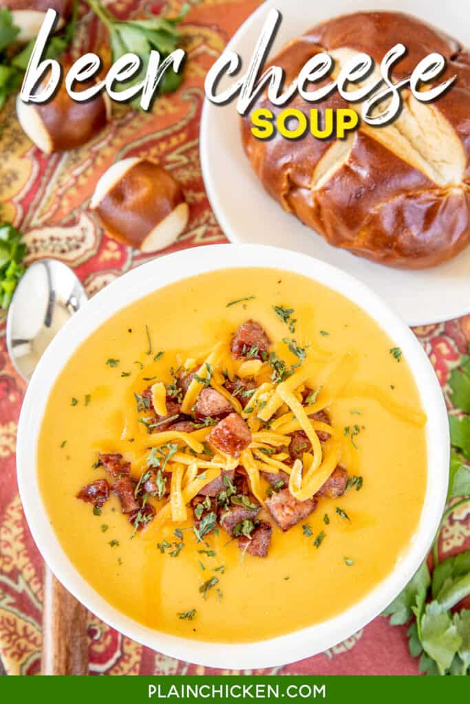 bowl of beer cheese and smoked sausage soup with a pretzel