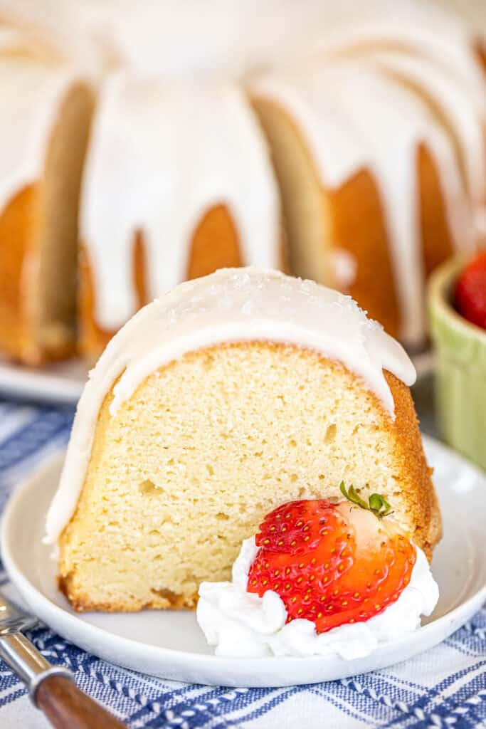 slice of iced pound cake on a plate with strawberries and whipped cream
