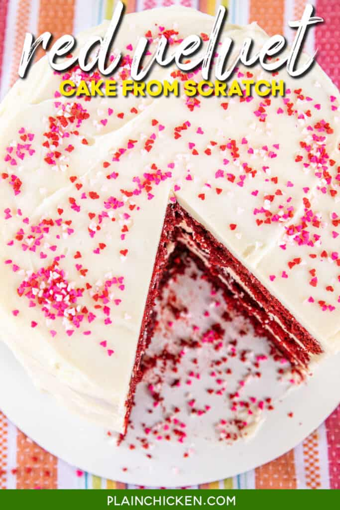 whole red velvet cake with a slice cut out of it