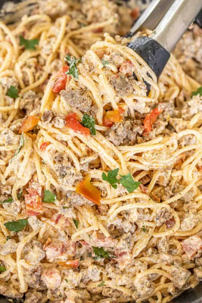 tongs in sausage and tomato pasta