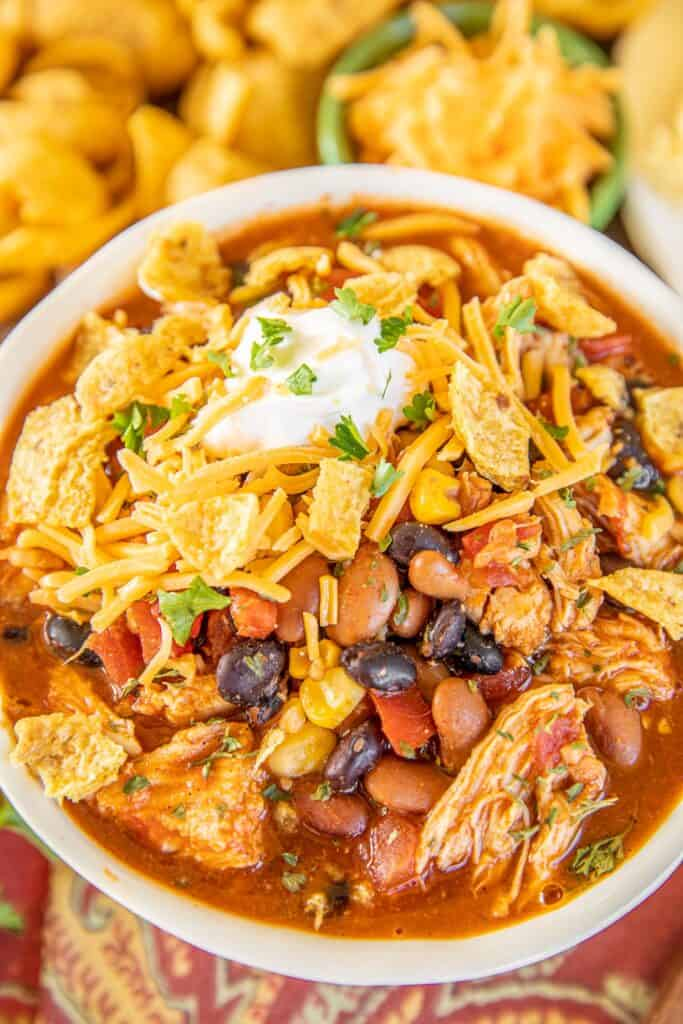 bowl of chicken chili with beans topped with sour cream and fritos