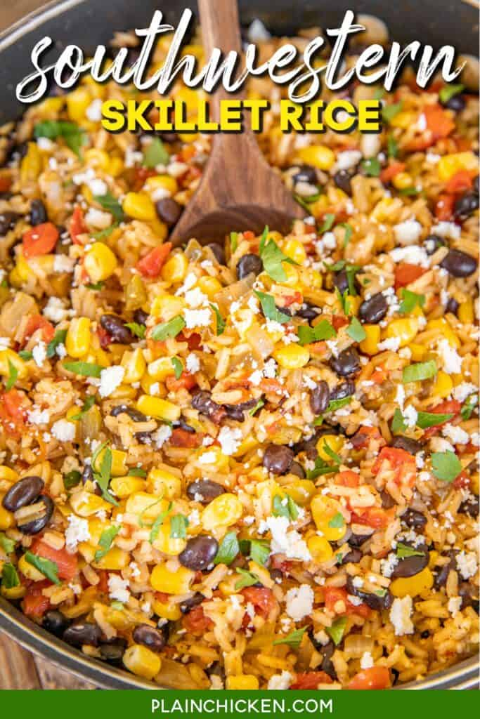spooning rice with black beans, peppers and corn from skillet