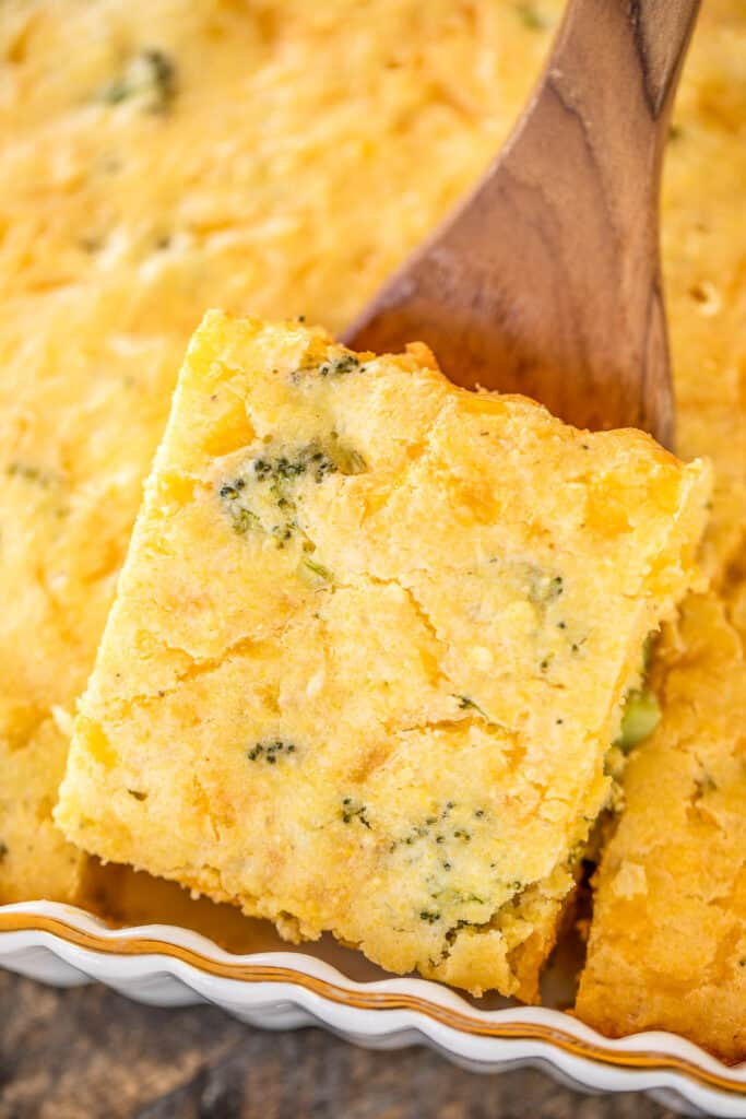 scooping broccoli cornbread from baking dish