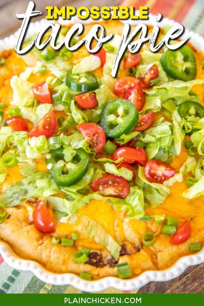 taco pie topped with lettuce and tomato in a pie plate