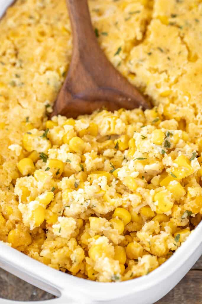scooping corn casserole from baking dish