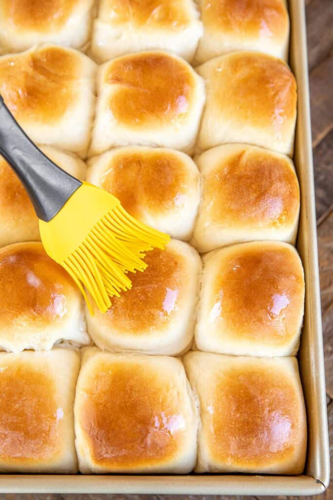 brushing yeast rolls with butter