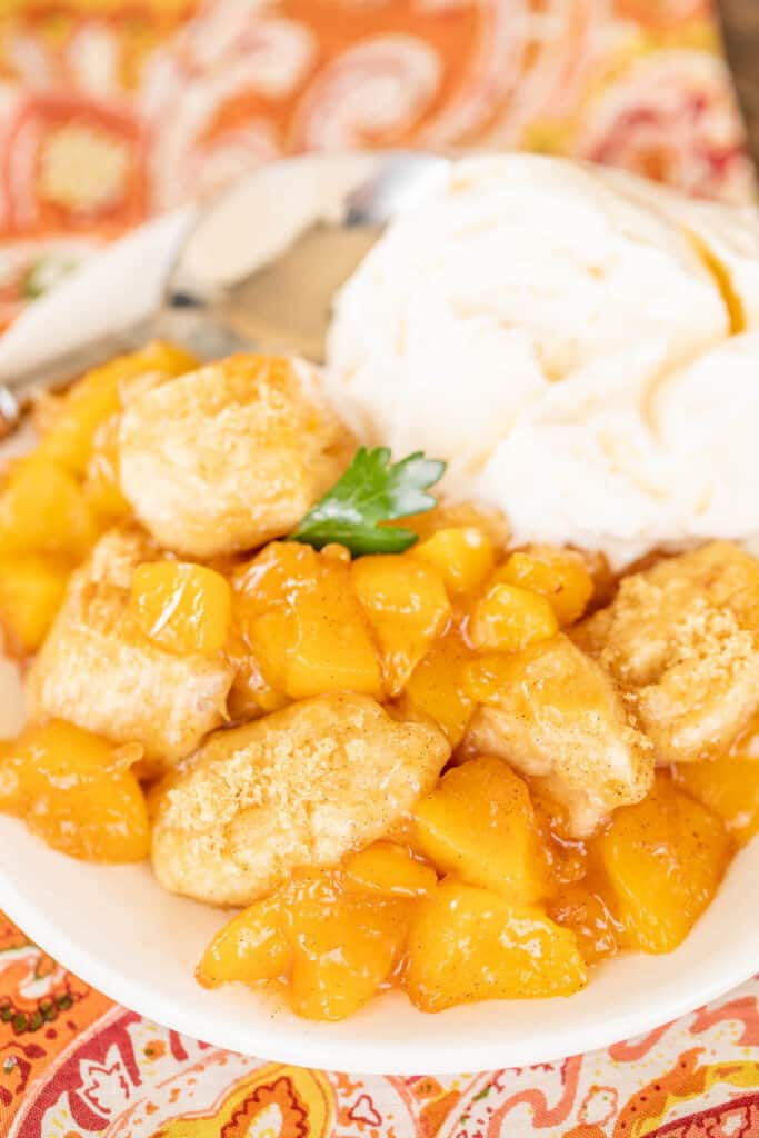 plate of biscuit peach cobbler bubble up with vanilla ice cream