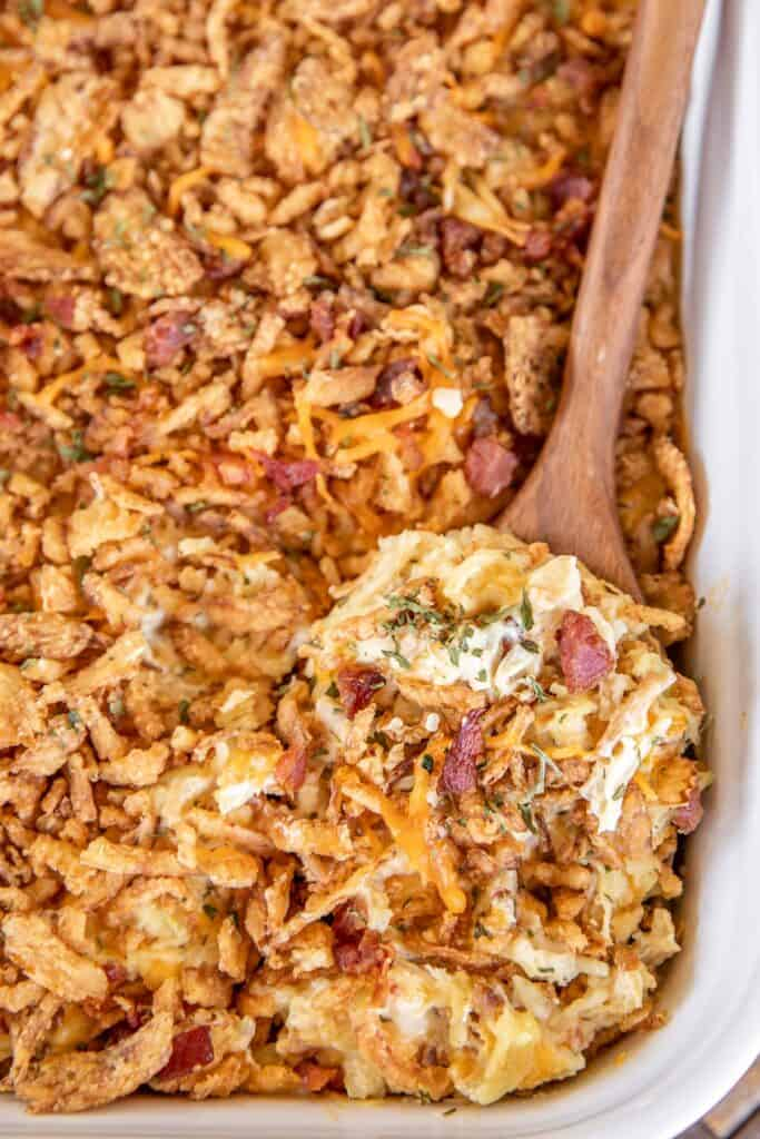 scooping chicken and rice casserole from baking dish