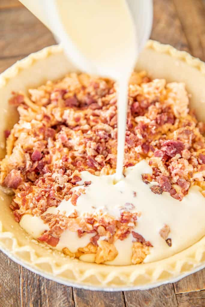 pouring egg custard into pie crust over pimento cheese & bacon