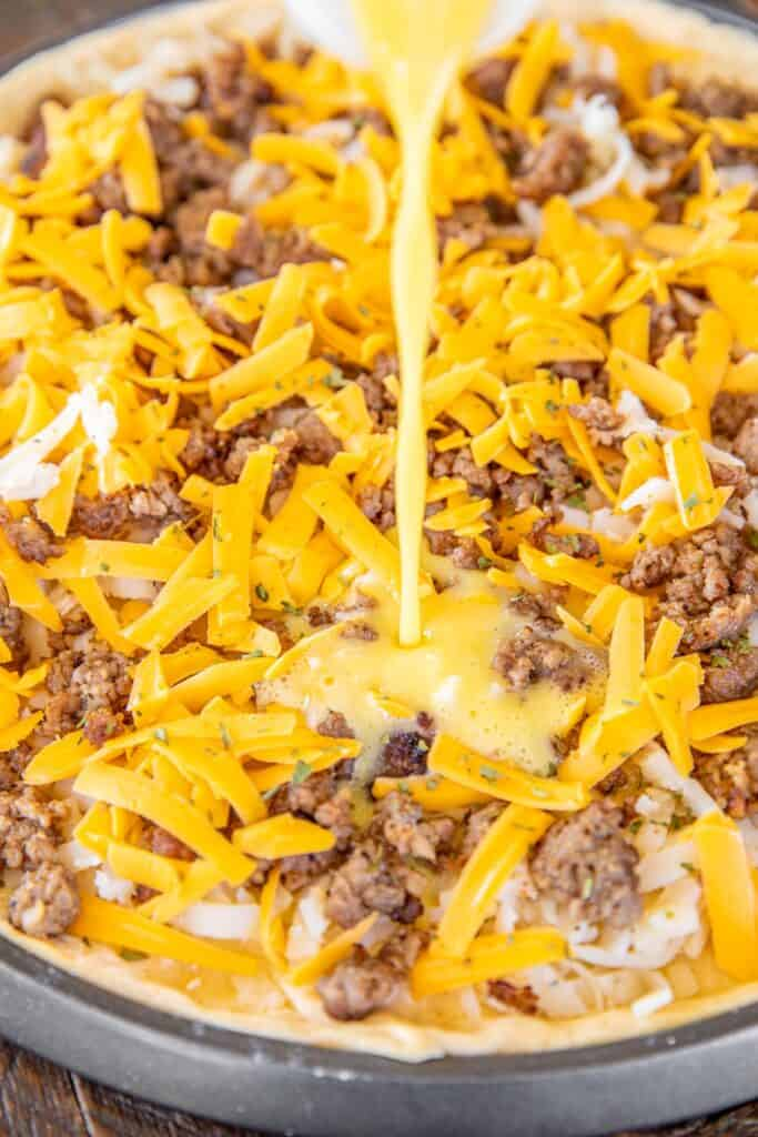 pouring egg custard over cheese sausage and hashbrowns