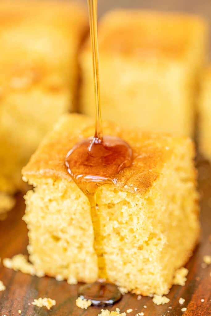 drizzling maple syrup over cornbread