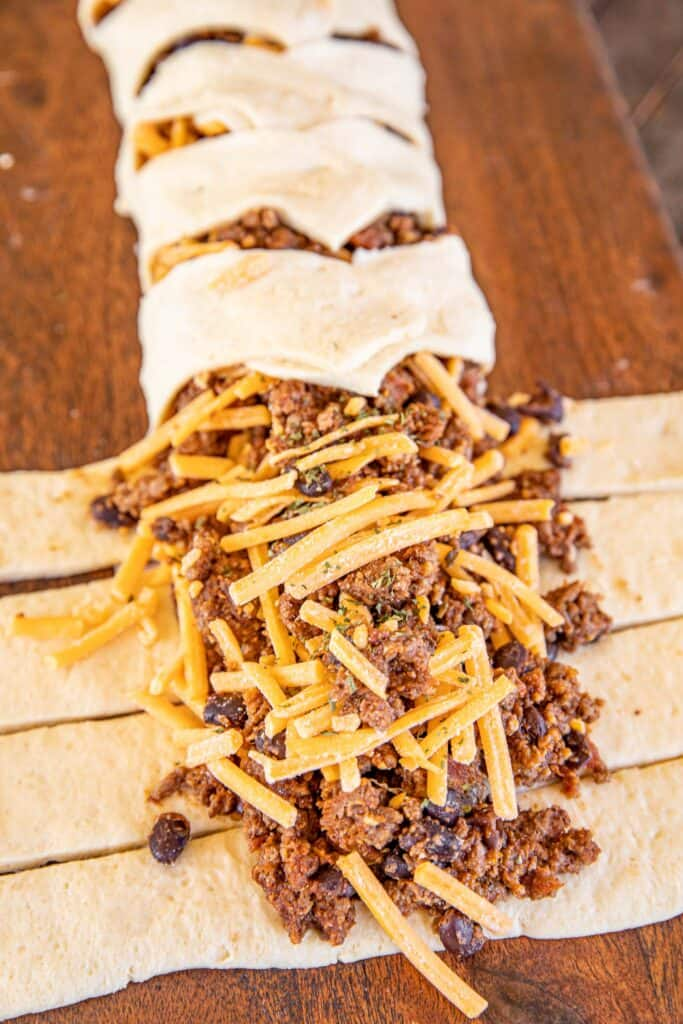taco meat and cheese on top of crescent rolls
