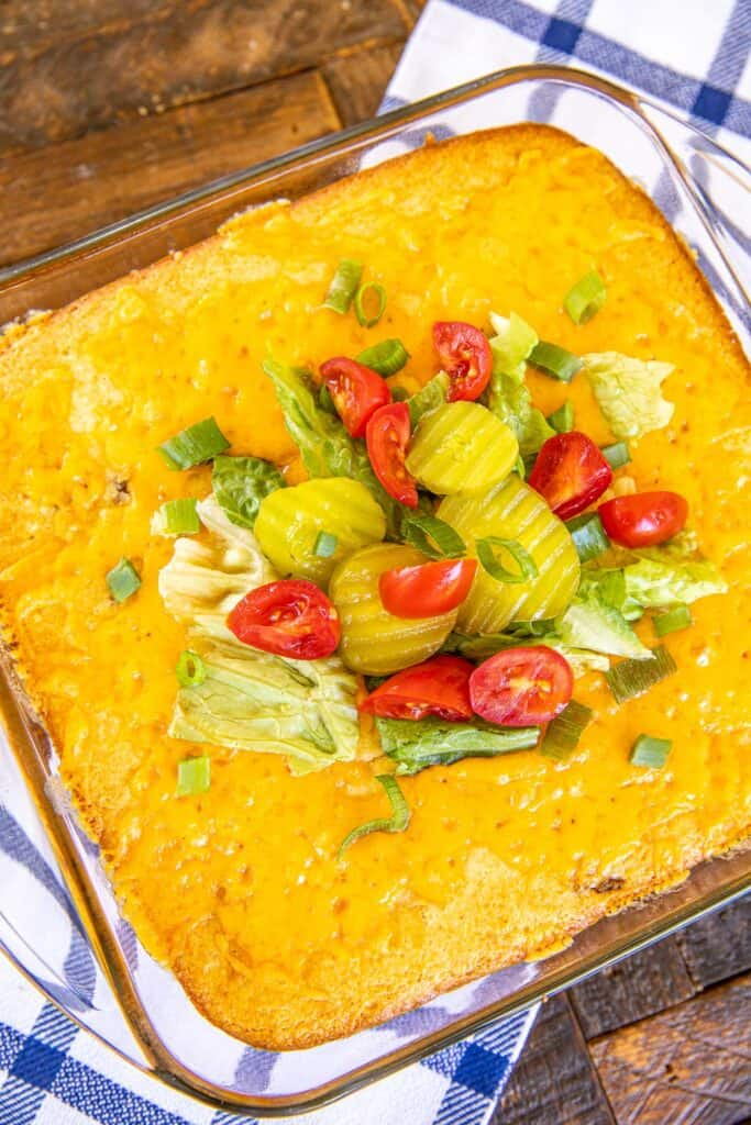 cornbread casserole in baking dish topped with lettuce tomatoes & pickles