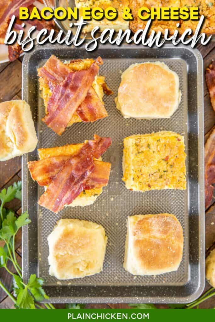 assembling bacon egg & cheese biscuit sandwiches on a baking sheet