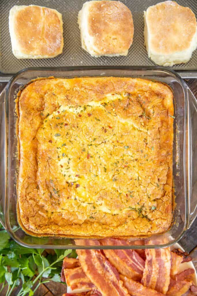 baking dish of baked egg casserole with biscuits and bacon around it