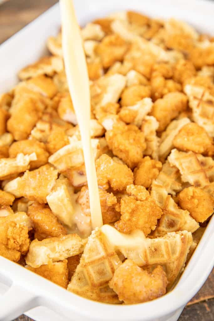 pouring egg custard over chicken and waffles in baking dish