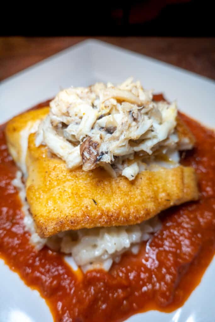 bowl of fried grouper over risotto and red sauce