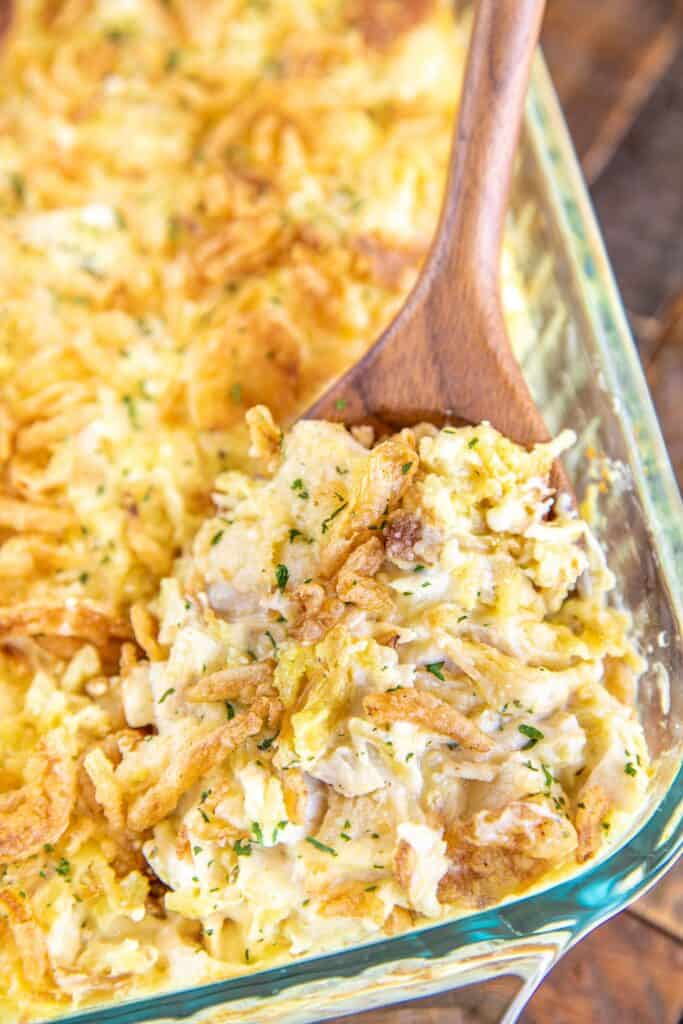 scooping chicken and rice from baking dish