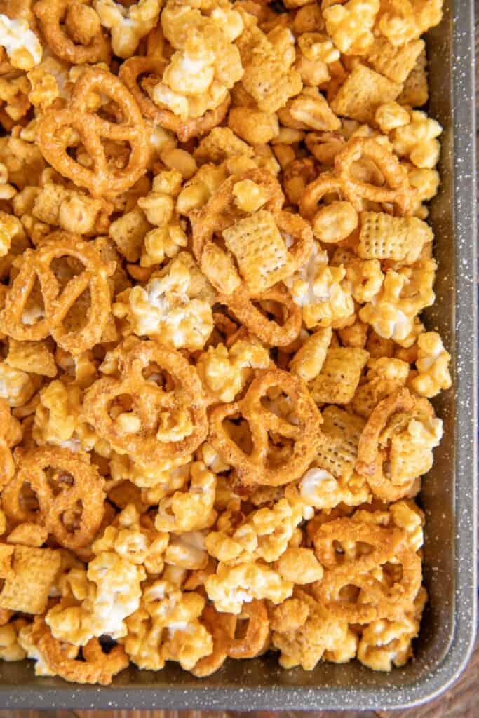 baking sheet of caramel pretzels popcorn and peanuts