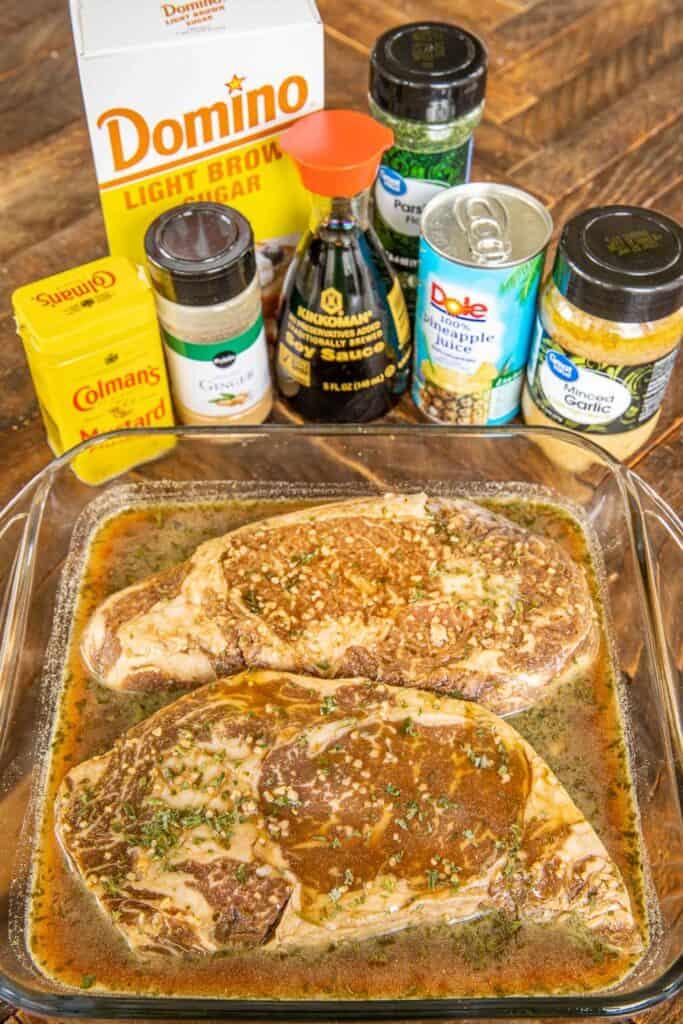 steak marinating in a pan with ingredients behind it