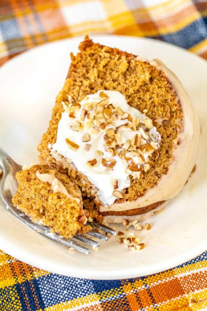 cutting a slice of sweet potato cake topped with whipped cream