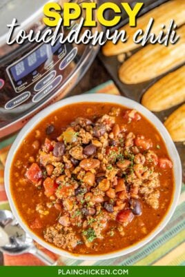 bowl of spicy chili with cornbread and a slow cooker in the back