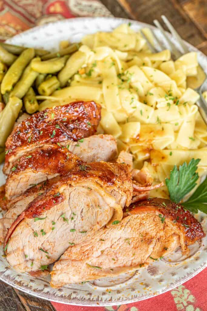 sliced bacon wrapped pork tenderloin on a plate with pasta and green beans